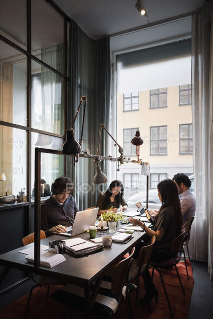 Creative business team sitting at table working in modern office — Stock Photo