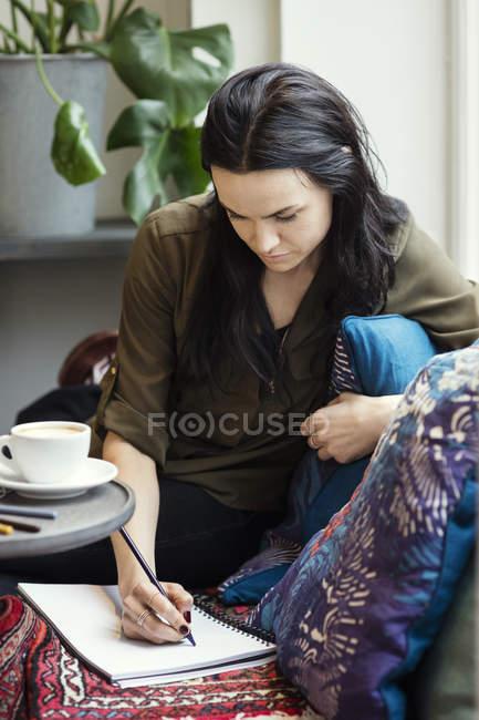 Konzentrierte Bloggerin schreibt auf dem Sofa im Spiralheft — Stockfoto