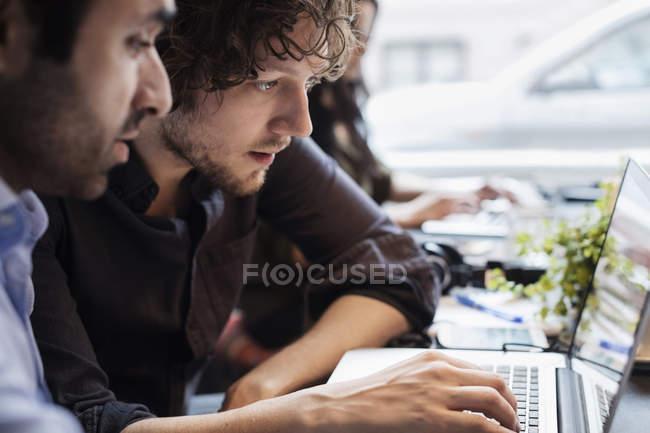 Концентровані бізнесмени використовують ноутбук на столі в креативному офісі — стокове фото