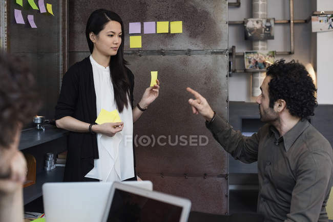 Creative businessman discussing with female coworker in office — Stock Photo