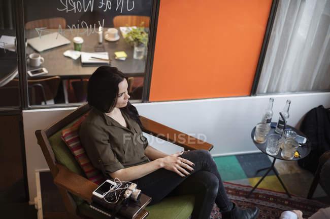Opinião de ângulo elevado a mulher de negócios criativa que senta-se na cadeira no escritório — Fotografia de Stock