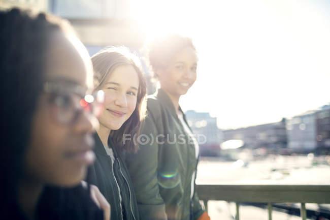 Teenager zwinkert beim Spazierengehen mit Freundinnen und schimpft gegen klaren Himmel — Stockfoto