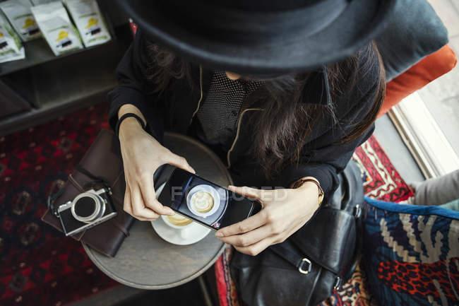 Diretamente acima do tiro da mulher jovem que fotografa o café pelo telefone inteligente no escritório criativo — Fotografia de Stock