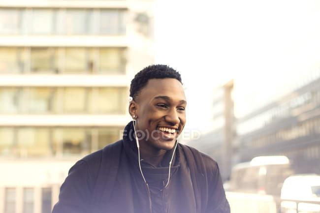 Adolescente feliz usando fones de ouvido em pé contra edifícios na cidade — Fotografia de Stock