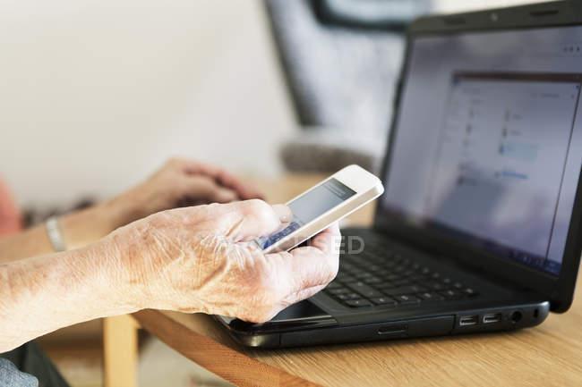 Imagen recortada de la mano de la mujer mayor usando el ordenador portátil y el teléfono en casa - foto de stock