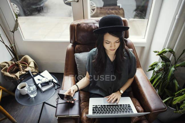 Opinião de ângulo elevado o trabalho creativo da mulher de negócios ao sentar-se na cadeira — Fotografia de Stock