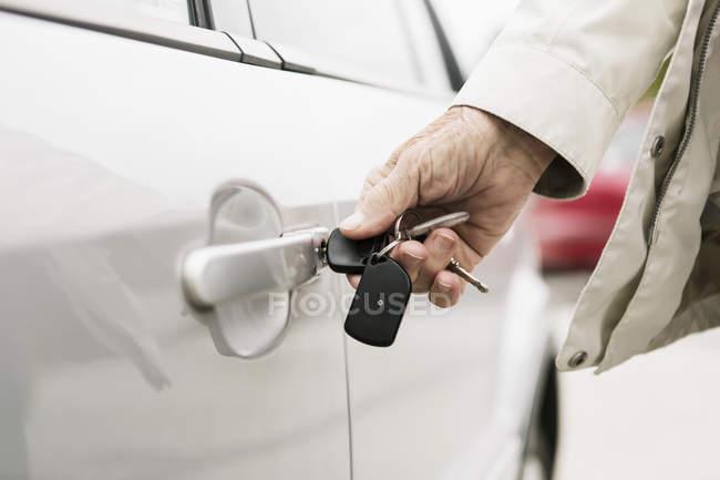 Immagine ritagliata della mano della donna anziana sbloccare la porta dell'auto — Foto stock