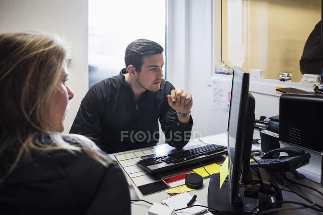 Propietaria que explica a las empresarias sobre el ordenador en el taller de reparación de automóviles. - foto de stock