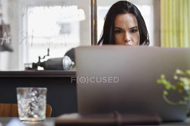 Konzentrierte Bloggerin mit Laptop am Tisch im Kreativbüro — Stockfoto
