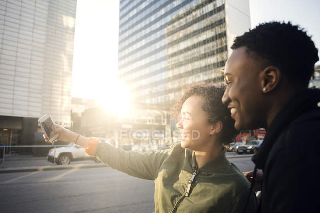 Teenager taking selfie with friend through smart phone by city street — Stock Photo