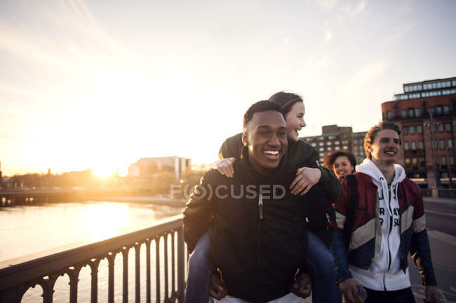 Smiling teenager piggybacking girl while walking with friends by canal — Stock Photo