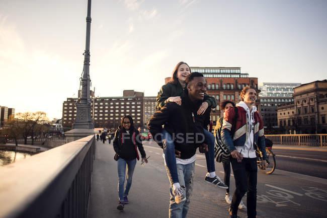 Feliz adolescente menino piggybacking amigo enquanto caminhando na ponte na cidade — Fotografia de Stock