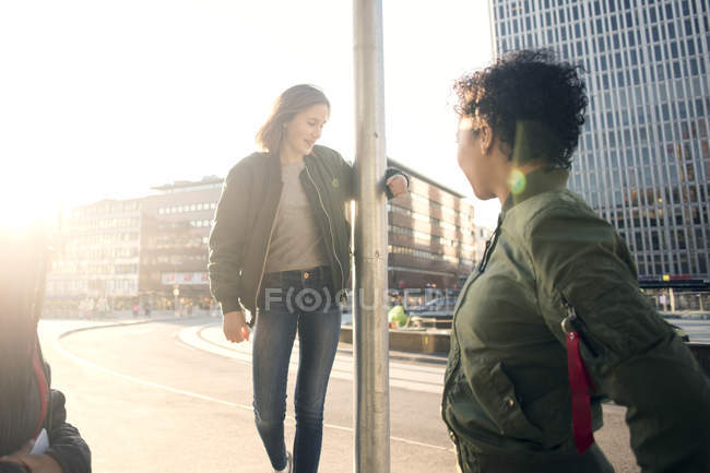 Friends are looking at teenage girl standing by pole against street and buildings — Stock Photo