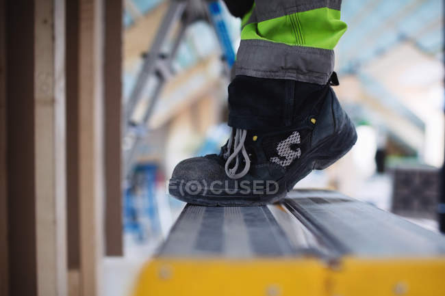 Low section of man wearing shoes standing on ladder — Stock Photo