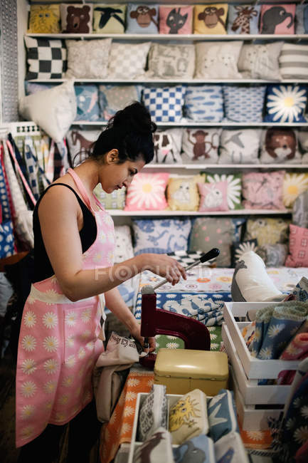 Side view of woman punching on textile while working in shop — Stockfoto