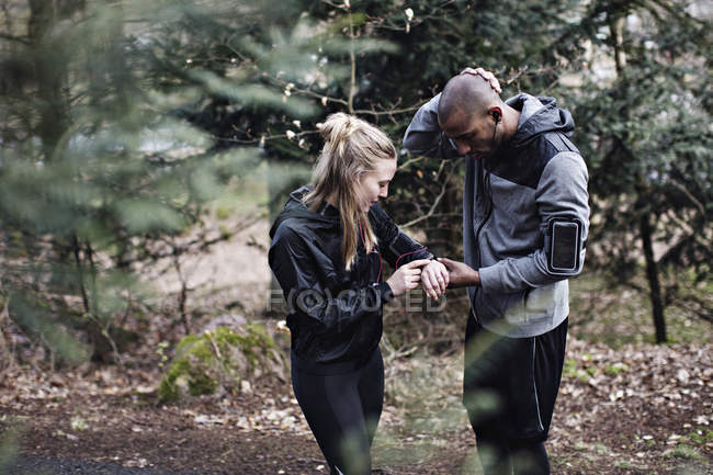 Male and female athletes checking smart watch in forest — Stock Photo