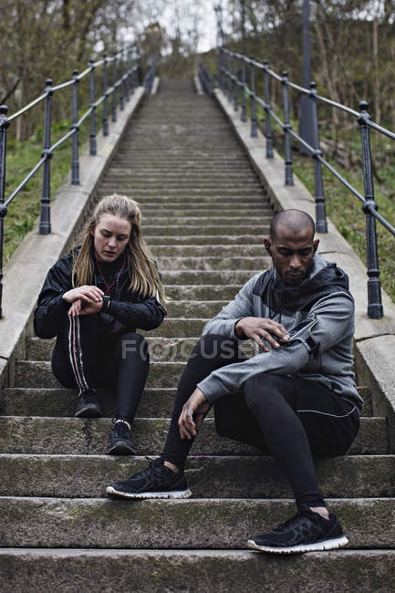 Full length of multi-ethnic couple checking wristwatch and mobile phone while sitting on steps — Stock Photo