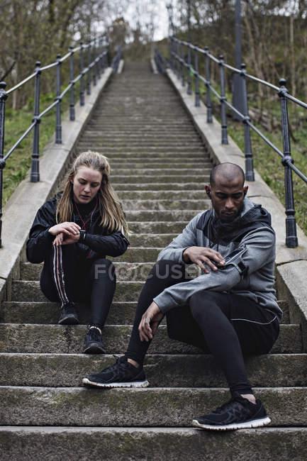 Полная длина многоэтнического пара, проверка наручные часы и мобильный телефон сидя на шагах — стоковое фото