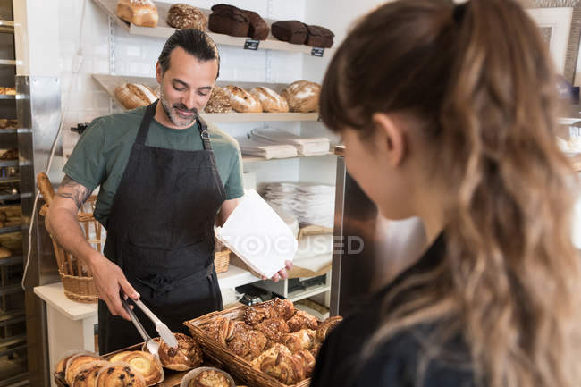 Smiling mature male owner serving fresh bread to female customer at bakery — Stock Photo