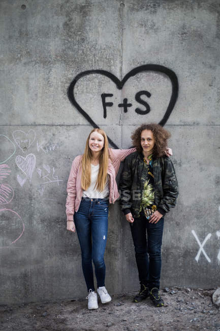 Full length portrait of smiling friends standing against graffiti on gray wall — Stock Photo