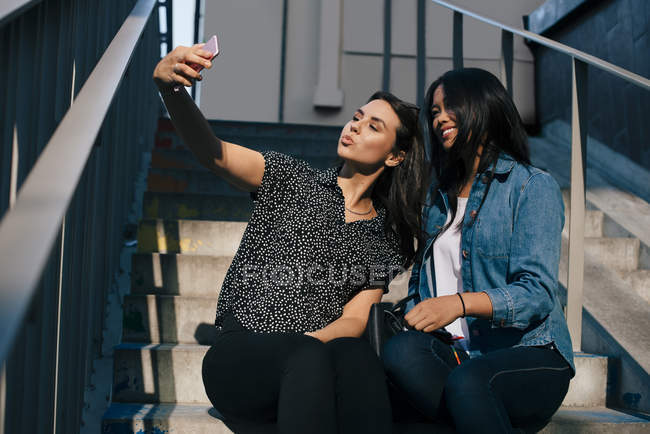 Low angle view of young woman taking selfie with female friend while sitting on staircase — Foto stock