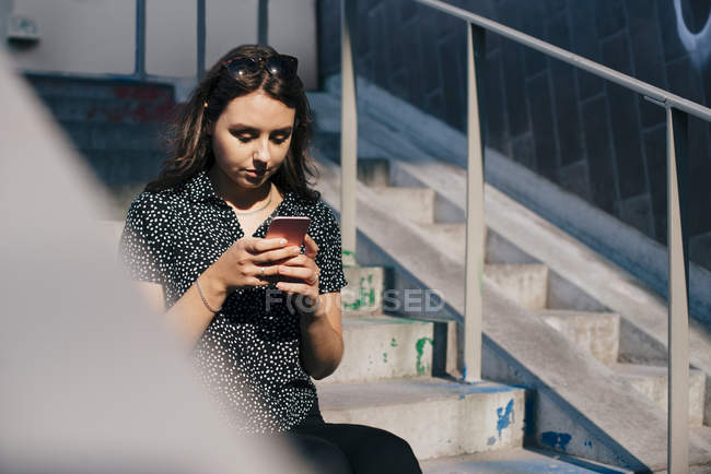 Young woman using smart phone while sitting on staircase during sunny day — Foto stock