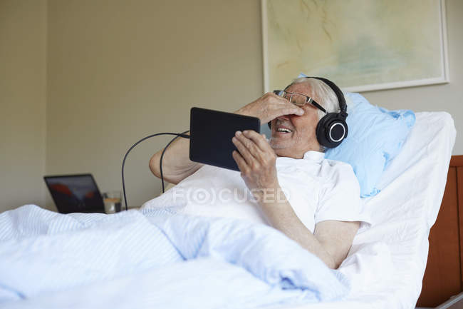 Senior man rubbing eyes while using digital tablet on bed in hospital ward — Stock Photo