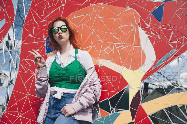 Portrait of redhead young woman wearing sunglasses while gesturing peace sign against mosaic wall — Stock Photo