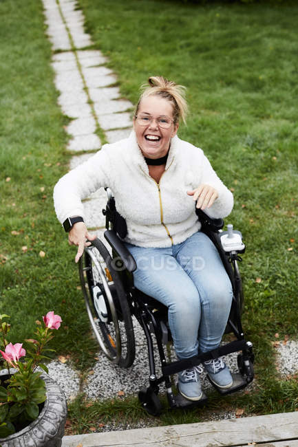 Full length portrait of smiling disabled woman sitting on wheelchair in yard — Stock Photo