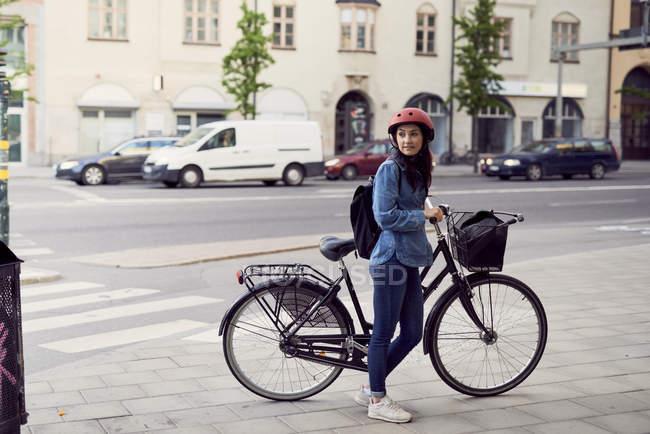 Mujer adulta de pie con bicicleta en la acera en la ciudad - foto de stock