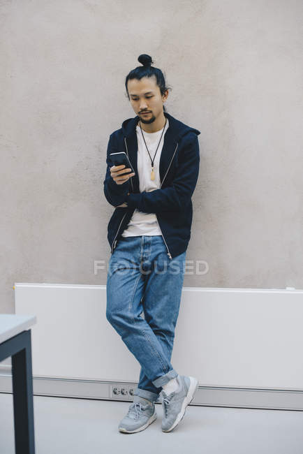Full length of male computer programmer using smart phone while leaning on beige wall in office — Stock Photo
