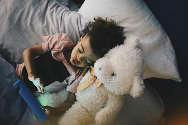 Vista de ángulo alto de niño acostado con oso de peluche mientras está usando la tableta digital en cama en casa - foto de stock