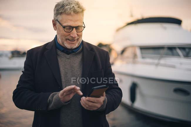 Uomo anziano utilizzando smart phone mentre in piedi al porto — Foto stock