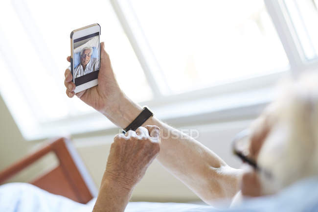 Cropped image of senior man taking selfie with smart phone in hospital ward — Stock Photo
