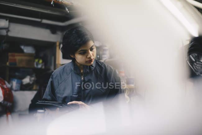 Female mechanic seen through open vehicle hood at auto repair shop — Stock Photo