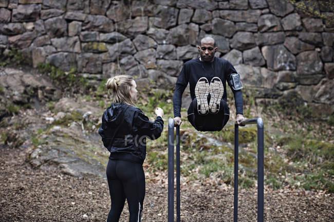 Вид сзади спортсменка, глядя на человека, осуществляя на брусья против каменной стеной в лесу — стоковое фото