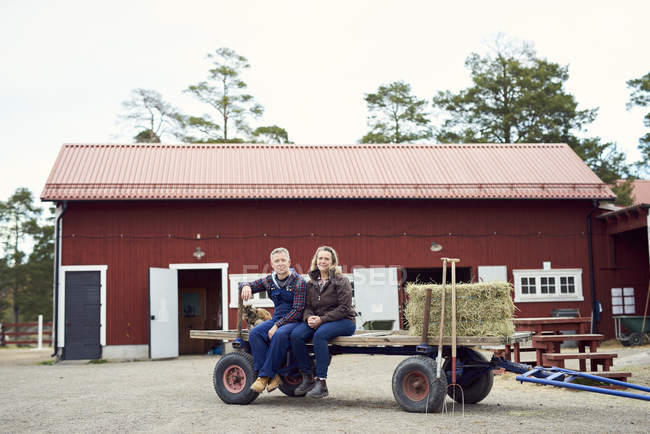 Mature couple sitting on old-fashioned trailer against barn — Photo de stock