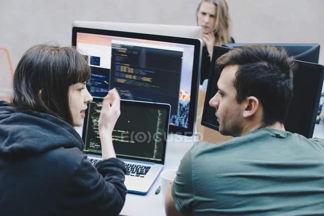 Vue arrière des programmeurs/programmeuses discuter au bureau — Photo de stock