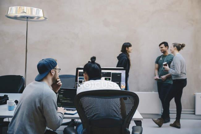 Programmeurs/programmeuses discutant au bureau créatif — Photo de stock