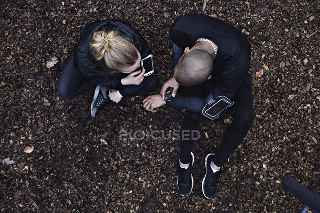 Directly above shot of couple using technologies while exercising in forest — Stock Photo