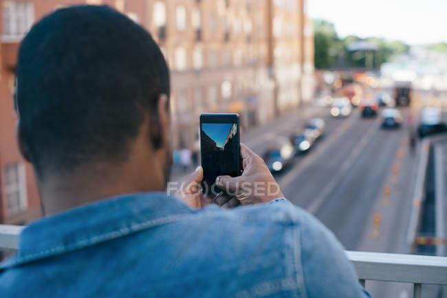 Vista trasera del hombre fotografiando la calle de la ciudad desde el teléfono móvil mientras está de pie en la pasarela - foto de stock