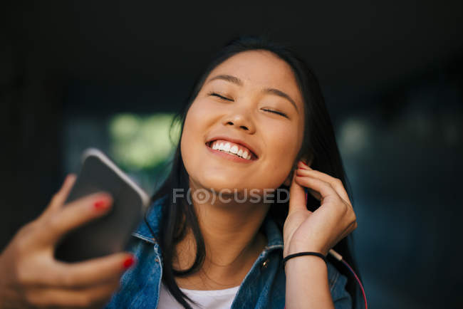 Cheerful teenage girl adjusting earphones while holding smart phone in city — Foto stock