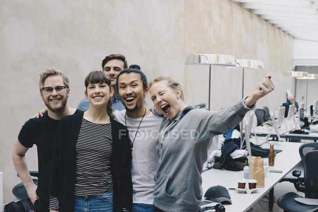 Programadora excitada gritando enquanto estava de pé com colegas no escritório — Fotografia de Stock