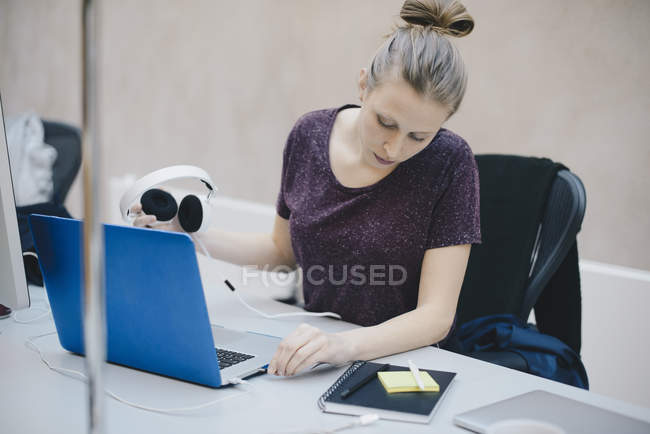 Female computer programmer connecting headphones to laptop at desk in office — стокове фото