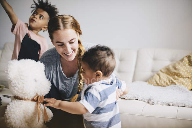 Smiling mother showing teddy bear to toddler while boy playing by sofa at home — Stock Photo