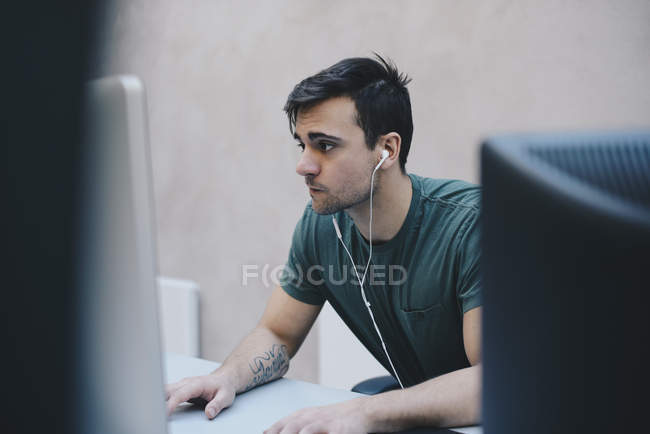 Computer programmer using desktop PC in office — Stock Photo