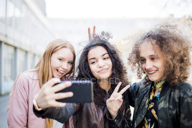 Smiling teenage girl taking selfie with friends from smart phone — Stock Photo