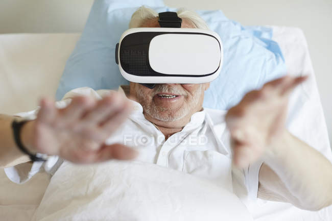 High angle view of senior man gesturing while using VR glasses on bed in hospital ward — Stock Photo