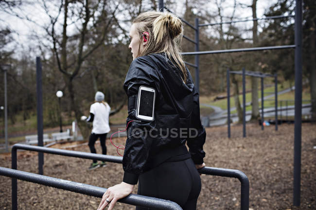 Vista posterior de atleta femenina lleva banda de brazo ejercicio en barras paralelas en bosque - foto de stock