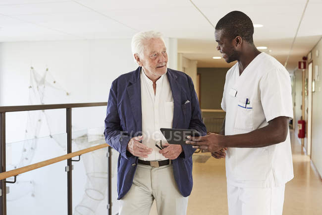 Male nurse and senior male patient discussing over digital tablet at hospital corridor — Stock Photo